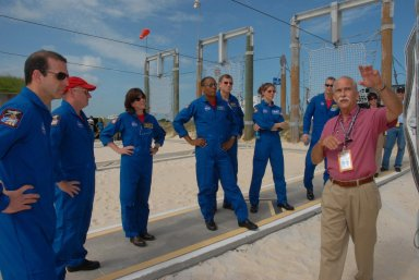 KENNEDY SPACE CENTER, Fla. -- Back on the slidewire landing area of Pad 39A, the STS-118 crew learns about landing in the baskets in the event of an emergency. From left are Mission Specialist Rick Mastracchio, Commander Scott Kelly, Mission Specialists Barbara R. Morgan, Alvin Drew, Dave Williams and Tracy Caldwell, and Pilot Charlie Hobaugh. Morgan joined NASA's Teacher in Space program in 1985 and was selected as an astronaut in 1998. Williams represents the Canadian Space Agency. The crew is at Kennedy for training activities in the terminal countdown demonstration test, or TCDT. TCDTactivities include M-113 training, payload familiarization, the emergency egress training at the pad and a simulated launch countdown. The mission is the 22nd flight to the International Space Station and Space Shuttle Endeavour will carry a payload including the S5 truss, a SPACEHAB module and external stowage platform 3. STS-118 is targeted for launch on Aug. 7. NASA/George Shelton