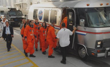 KENNEDY SPACE CENTER, Fla. -- The STS-118 crew heads into the Astrovan that will take them to Launch Pad 39A for a simulated launch countdown. First in is Commander Scott Kelly. Following, right to left, are Pilot Charlie Hobaugh and Mission Specialists Tracy Caldwell, Dave Williams, Rick Mastracchio, teacher-turned-astronaut Barbara R. Morgan and Alvin Drew. The countdown concludes the terminal countdown demonstration test, or TCDT. The STS-118 crew has been at Kennedy for the TCDT activities that also include M-113 training, payload familiarization and emergency egress training at the pad. The mission is the 22nd flight to the International Space Station and Space Shuttle Endeavour will carry a payload including the S5 truss, a SPACEHAB module and external stowage platform 3. STS-118 is targeted for launch on Aug. 7. Photo credit: NASA/George Shelton
