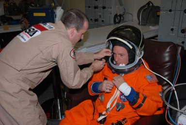 KENNEDY SPACE CENTER, Fla. -- STS-118 Commander Scott Kelly gets help suiting up before the simulated launch countdown that concludes the terminal countdown demonstration test, or TCDT. The STS-118 crew has been at Kennedy for the TCDT activities that also include M-113 training, payload familiarization and emergency egress training at the pad. The mission is the 22nd flight to the International Space Station and Space Shuttle Endeavour will carry a payload including the S5 truss, a SPACEHAB module and external stowage platform 3. STS-118 is targeted for launch on Aug. 7. Photo credit: NASA/George Shelton