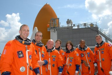 KENNEDY SPACE CENTER, Fla. -- On top of the fixed service structure of Launch Pad 39A, The STS-118 crew poses for a photo after conclusion of the terminal countdown demonstration test. From left are Pilot Charlie Hobaugh, Mission Specialist Rick Mastracchio, Commander Scott Kelly, and Mission Specialists Tracy Caldwell, Barbara R. Morgan, Alvin Drew and Dave Williams. Morgan, who is making her first space flight, joined NASA's Teacher in Space program in 1985 and was selected as an astronaut in 1998. Williams represents the Canadian Space Agency. The STS-118 mission on Space Shuttle Endeavour is the 22nd flight to the International Space Station and will carry a payload including the S5 truss, a SPACEHAB module and external stowage platform 3. STS-118 is targeted for launch on Aug. 7. Photo credit: NASA/George Shelton