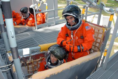 KENNEDY SPACE CENTER, Fla. -- Practicing emergency egress from Launch Pad 39A, STS-118 Mission Specialists Tracy Caldwell (left) and Rick Mastracchio are seated in a slidewire basket in the foreground. Others in the background include Mission Specialist Barbara R. Morgan (center). Other crew members are Commander Scott Kelly, Pilot Charlie Hobaugh and Mission Specialists Dave Williams and Alvin Drew. Morgan joined NASA's Teacher in Space program in 1985 and was selected as an astronaut in 1998. Williams represents the Canadian Space Agency. The STS-118 mission on Space Shuttle Endeavour is the 22nd flight to the International Space Station and will carry a payload including the S5 truss, a SPACEHAB module and external stowage platform 3. STS-118 is targeted for launch on Aug. 7. Photo credit: NASA/George Shelton