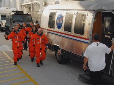 KENNEDY SPACE CENTER, Fla. -- The STS-118 crew walks toward the Astrovan that will take them to Launch Pad 39A for a simulated launch countdown. On the left are Pilot Charlie Hobaugh leading the way and Mission Specialist Rick Mastracchio. ON the right, Commander Scott Kelly leads with (front to back) Mission Specialists Tracy Caldwell, Dave Williams and Alvin Drew. Not visible is teacher-turned-astronaut Barbara R. Morgan, also a mission specialist. The countdown concludes the terminal countdown demonstration test, or TCDT. The STS-118 crew has been at Kennedy for the TCDT activities that also include M-113 training, payload familiarization and emergency egress training at the pad. The mission is the 22nd flight to the International Space Station and Space Shuttle Endeavour will carry a payload including the S5 truss, a SPACEHAB module and external stowage platform 3. STS-118 is targeted for launch on Aug. 7. Photo credit: NASA/George Shelton