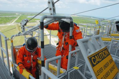 KENNEDY SPACE CENTER, Fla. -- Practicing emergency egress from Launch Pad 39A, STS-118 crew members climb into a slidewire basket. They are taking part in terminal countdown demonstration test activities that included a simulated launch countdown. The crew comprises Commander Scott Kelly, Pilot Charlie Hobaugh and Mission Specialists Dave Williams, Barbara R. Morgan, Rick Mastracchio, Tracy Caldwell and Alvin Drew. Williams represents the Canadian Space Agency. Morgan joined NASA's Teacher in Space program in 1985 and was selected as an astronaut in 1998. The STS-118 mission on Space Shuttle Endeavour is the 22nd flight to the International Space Station and will carry a payload including the S5 truss, a SPACEHAB module and external stowage platform 3. STS-118 is targeted for launch on Aug. 7. Photo credit: NASA/George Shelton