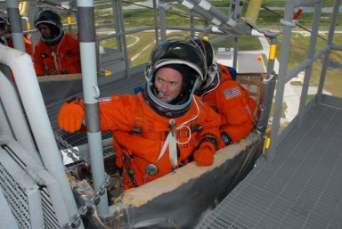 KENNEDY SPACE CENTER, Fla. -- Practicing emergency egress from Launch Pad 39A, STS-118 Commander Scott Kelly (left) reaches for the pull lever of the slidewire basket. Behind him is Pilot Charlie Hobaugh. At upper left in another basket is Mission Specialist Rick Mastracchio. Other crew members are Mission Specialists Dave Williams, Barbara R. Morgan, Tracy Caldwell and Alvin Drew. Morgan joined NASA's Teacher in Space program in 1985 and was selected as an astronaut in 1998. Williams represents the Canadian Space Agency. The STS-118 mission on Space Shuttle Endeavour is the 22nd flight to the International Space Station and will carry a payload including the S5 truss, a SPACEHAB module and external stowage platform 3. STS-118 is targeted for launch on Aug. 7. NASA/George Shelton