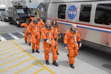 KENNEDY SPACE CENTER, FLA. -- The suited STS-118 crew moves quickly to the Astrovan after leaving the Operations and Checkout Building. From left are Mission Specialists Barbara R. Morgan, Rick Mastracchio and Dave Williams, Pilot Charlie Hobaugh, Mission Specialist Tracy Caldwell and Commander Scott Kelly. Behind Williams is Mission Specialist Alvin Drew. The Astrovan will take them to Launch Pad 39A for final suit preparations before climbing into Space Shuttle Endeavour for launch at 6:36 p.m. EDT. The STS-118 mission is the 22nd shuttle flight to the International Space Station. It will continue space station construction by delivering a third starboard truss segment, S5, and other payloads such as the SPACEHAB module and the external stowage platform 3. The 11-day mission may be extended to as many as 14 depending on the test of the Station-to-Shuttle Power Transfer System that will allow the docked shuttle to draw electrical power from the station and extend its visits to the orbiting lab. NASA/Kim Shiflett