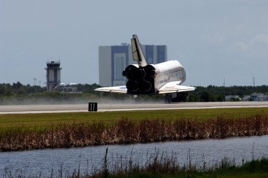 KENNEDY SPACE CENTER, FLA. -- Endeavour passes the air traffic control tower (left) next to the Shuttle Landing Facility as it touches down on runway 15 at NASA's Kennedy Space Center after traveling nearly 5.3 million miles on mission STS-118. Behind Endeavour is the Vehicle Assembly Building. The Space Shuttle Endeavour crew, led by Commander Scott Kelly, completes a 13-day mission to the International Space Station. The STS-118 mission began Aug. 8 and installed a new gyroscope, an external spare parts platform and another truss segment to the expanding station. Endeavour's main gear touched down at 12:32:16 p.m. EDT. Nose gear touchdown was at 12:32:29 p.m. and wheel stop was at 12:33:20 p.m. Endeavour landed on orbit 201. STS-118 was the 119th space shuttle flight, the 22nd flight to the station, the 20th flight for Endeavour and the second of four missions planned for 2007. This was the 65th landing of an orbiter at Kennedy. Photo credit: NASA/Rafael Hernandez