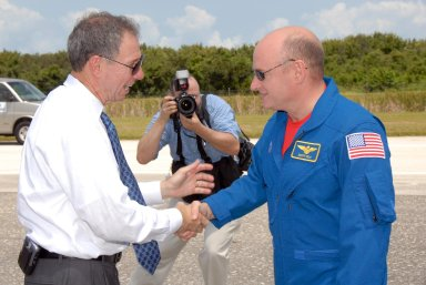 KENNEDY SPACE CENTER, FLA. -- A photographer captures the moment as NASA Administrator Mike Griffin (left) welcomes STS-118 Commander Scott Kelly back to Earth after completing mission STS-118. On the mission, the crew installed a new gyroscope, an external spare parts platform and another truss segment to the expanding station. Endeavour's main gear touched down at 12:32:16 p.m. EDT. Nose gear touchdown was at 12:32:29 p.m. and wheel stop was at 12:33:20 p.m. Endeavour landed on orbit 201. STS-118 was the 119th space shuttle flight, the 22nd flight to the station, the 20th flight for Endeavour and the second of four missions planned for 2007. This was the 65th landing of an orbiter at Kennedy. Photo credit: NASA/Kim Shiflett