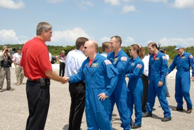 KENNEDY SPACE CENTER, FLA. -- The STS-118 crew is welcomed back to Earth by NASA officials after completing mission STS-118. From left are KSC Director Bill Parsons, Mission Launch Integration Director Leroy Cain, Commander Scott Kelly, Shuttle Launch Director Mike Leinbach, Pilot Charlie Hobaugh, and Mission Specialists Tracy Caldwell, Rick Mastracchio and Canadian astronaut Dave Williams. NASA Administrator Mike Griffin also greeted the astronauts. On the mission, the crew installed a new gyroscope, an external spare parts platform and another truss segment to the expanding station. Endeavour's main gear touched down at 12:32:16 p.m. EDT. Nose gear touchdown was at 12:32:29 p.m. and wheel stop was at 12:33:20 p.m. Endeavour landed on orbit 201. STS-118 was the 119th space shuttle flight, the 22nd flight to the station, the 20th flight for Endeavour and the second of four missions planned for 2007. This was the 65th landing of an orbiter at Kennedy. Photo credit: NASA/Kim Shiflett