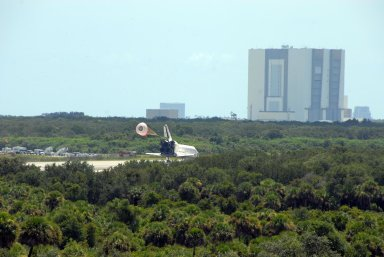 KENNEDY SPACE CENTER, FLA. -- The open drag chute helps slow Endeavour as it lands on runway 15 at NASA's Kennedy Space Center after traveling nearly 5.3 million miles on mission STS-118. In the background, at right, is the Vehicle Assembly Building. The Space Shuttle Endeavour crew, led by Commander Scott Kelly, completes a 13-day mission to the International Space Station. The STS-118 mission began Aug. 8 and installed a new gyroscope, an external spare parts platform and another truss segment to the expanding station. Endeavour's main gear touched down at 12:32:16 p.m. EDT. Nose gear touchdown was at 12:32:29 p.m. and wheel stop was at 12:33:20 p.m. Endeavour landed on orbit 201. STS-118 was the 119th space shuttle flight, the 22nd flight to the station, the 20th flight for Endeavour and the second of four missions planned for 2007. This was the 65th landing of an orbiter at Kennedy. Photo credit: NASA/Ken Thornsley