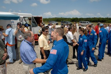 KENNEDY SPACE CENTER, FLA. -- The STS-118 crew is welcomed back to Earth by NASA officials after completing mission STS-118. The crew members are (from front) Pilot Charlie Hobaugh, Commander Scott Kelly, and Mission Specialists Tracy Caldwell, Rick Mastracchio and Canadian astronaut Dave Williams. Williams is talking to Laurier Boisvert, president of the Canadian Space Agency. On the mission, the crew installed a new gyroscope, an external spare parts platform and another truss segment to the expanding station. Endeavour's main gear touched down at 12:32:16 p.m. EDT. Nose gear touchdown was at 12:32:29 p.m. and wheel stop was at 12:33:20 p.m. Endeavour landed on orbit 201. STS-118 was the 119th space shuttle flight, the 22nd flight to the station, the 20th flight for Endeavour and the second of four missions planned for 2007. This was the 65th landing of an orbiter at Kennedy. Photo credit: NASA/Kim Shiflett