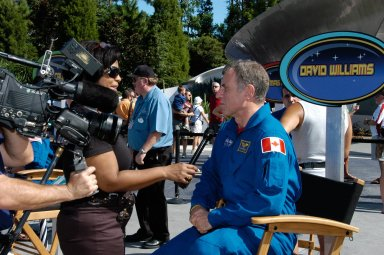 KENNEDY SPACE CENTER, FLA. -- A reporter interviews STS-118 Mission Specialist Dave Williams during a special event at Walt Disney World in Orlando . The day's events honoring the STS-118 space shuttle crew recognized the inspirational achievement of teacher-turned-astronaut Barbara R. Morgan who helped dedicate a plaque outside the Mission: Space attraction, and included meeting with students and the media and parading down Main Street to the delight of the crowds. The other crew members attending were Commander Scott Kelly, Pilot Charlie Hobaugh and Mission Specialists Tracy Caldwell, Rick Mastracchio and Alvin Drew. Mission STS-118 was the 119th shuttle program flight and the 22nd flight to the International Space Station. Space shuttle Endeavour launched from NASA's Kennedy Space Center on Aug. 8 and landed Aug. 21. The mission delivered the S5 truss, continuing the assembly of the space station. Photo credit: NASA/George Shelton