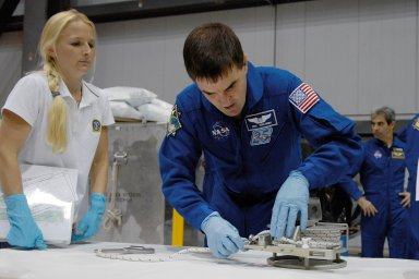 KENNEDY SPACE CENTER, FLA. -- In the Orbiter Processing Facility, STS-122 Mission Specialist Rex Walheim practices working with equipment for the mission. In the background, at right, is European Space Agency astronaut Leopold Eyharts, who will be on the mission and joining the Expedition 16 crew as flight engineer on the International Space Station. The crew is at Kennedy Space Center to take part in a crew equipment interface test, which includes equipment familiarization. The mission will carry and install the Columbus Lab, a multifunctional, pressurized laboratory that will be permanently attached to Node 2 of the space station to carry out experiments in materials science, fluid physics and biosciences, as well as to perform a number of technological applications. It is Europe?s largest contribution to the construction of the International Space Station and will support scientific and technological research in a microgravity environment. STS-122 is targeted for launch in December. Photo credit: NASA/Kim Shiflett