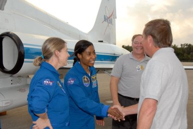 KENNEDY SPACE CENTER, FLA. -- The crew members of mission STS-120 arrive at NASA's Kennedy Space Center Shuttle Landing Facility aboard T-38 jet aircraft to take part in terminal countdown demonstration test activities. Shuttle Launch Director Michael Leinbach shakes hands with Mission Specialist Stephanie Wilson, who will be making her second shuttle flight, as Commander Pam Melroy, at left, looks on. The terminal countdown demonstration test provides astronauts and ground crews an opportunity to participate in various simulated countdown activities, including equipment familiarization and emergency training. The STS-120 mission will deliver the U.S. Node 2 module, named Harmony, aboard space shuttle Discovery to the International Space Station. Launch of Discovery on mission STS-120 is targeted for Oct. 23 at 11:38 a.m. EDT on a 14-day mission to the International Space Station. Photo credit: NASA/Kim Shiflett