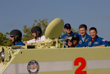 KENNEDY SPACE CENTER, FLA. -- STS-120 Pilot George Zamka practices driving the M-113 armored personnel carrier, part of emergency exit procedures from Launch Pad 39A. Alongside is the trainer. In the rear of the M-113 are Mission Specialists Daniel Tani, Commander Pamela Melroy and Mission Specialists Stephanie Wilson, Paolo Nespoli and Doug Wheelock. Nespoli represents the European Space Agency. The training is part of terminal countdown demonstration test, or TCDT, activities the crew is undertaking at NASA's Kennedy Space Center. The TCDT also includes equipment familiarization and a simulated launch countdown. Mission STS-120, which will carry the Italian-built U.S. Node 2 to the International Space Station, is targeted for launch on Oct. 23. Photo credit: NASA/Kim Shiflett