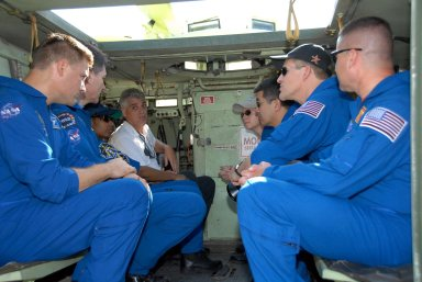 KENNEDY SPACE CENTER, FLA. -- STS-120 crew members listen to instructions about the use of the M-113 armored personnel carrier for emergency exit procedures from Launch Pad 39A. From the front, on the left, are Mission Specialists Doug Wheelock, Paolo Nespoli and Stephanie Wilson; at right are Pilot George Zamka, Mission Specialists Scott Parazynski and Daniel Tani, and Commander Pamela Melroy. Nespoli represents the European Space Agency. The training is part of terminal countdown demonstration test, or TCDT, activities the crew is undertaking at NASA's Kennedy Space Center. The TCDT also includes equipment familiarization and a simulated launch countdown. Mission STS-120, which will carry the Italian-built U.S. Node 2 to the International Space Station, is targeted for launch on Oct. 23. Photo credit: NASA/Kim Shiflett