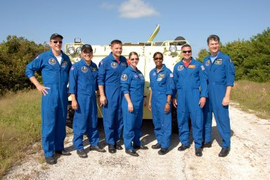 KENNEDY SPACE CENTER, FLA. -- After driving practice on the M-113 armored personnel carrier, the STS-120 crew pauses for a group photo. From left are Mission Specialists Scott Parazynski, Daniel Tani and Doug Wheelock, Commander Pamela Melroy, Mission Specialist Stephanie Wilson, Pilot George Zamka and Mission Specialist Paolo Nespoli, who represents the European Space Agency. The M-113 is part of emergency exit procedures from Launch Pad 39A. The training is part of terminal countdown demonstration test, or TCDT, activities the crew is undertaking at NASA's Kennedy Space Center. The TCDT also includes equipment familiarization and a simulated launch countdown. Mission STS-120, which will carry the Italian-built U.S. Node 2 to the International Space Station, is targeted for launch on Oct. 23. Photo credit: NASA/Kim Shiflett
