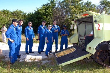 KENNEDY SPACE CENTER, FLA. -- Outside the M-113 armored personnel carrier, STS-120 crew members listen to instructions on its use for emergency exit procedures from Launch Pad 39A. From left are Mission Specialists Daniel Tani and Doug Wheelock, Pilot George Zamka, Mission Specialist Scott Parazynski, Commander Pamela Melroy, and Mission Specialists Paolo Nespoli and Stephanie Wilson. Nespoli represents the European Space Agency. The training is part of terminal countdown demonstration test, or TCDT, activities the crew is undertaking at NASA's Kennedy Space Center. The TCDT also includes equipment familiarization and a simulated launch countdown. Mission STS-120, which will carry the Italian-built U.S. Node 2 to the International Space Station, is targeted for launch on Oct. 23. Photo credit: NASA/Kim Shiflett