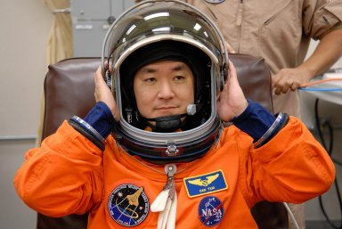 KENNEDY SPACE CENTER, FLA. -- STS-120 Mission Specialist Daniel Tani tries on his helmet with his launch and entry suit, preparing for launch. The fitting is part of terminal countdown demonstration test, or TCDT, activities the crew is undertaking at NASA's Kennedy Space Center. The TCDT also includes emergency egress procedures, equipment familiarization and a simulated launch countdown. Mission STS-120, which will carry the Italian-built U.S. Node 2 to the International Space Station, is targeted for launch on Oct. 23. Photo credit: NASA/Kim Shiflett