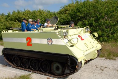KENNEDY SPACE CENTER, FLA. -- STS-120 Mission Specialist Paolo Nespoli, who represents the European Space Agency, practices driving the M-113 armored personnel carrier, which is part of emergency exit procedures from Launch Pad 39A. Also in front is the trainer. Passenger crew members in the rear are (from left) Mission Specialists Daniel Tani, Commander Pamela Melroy, Mission Specialist Scott Parazynski and Pilot George Zamka. The training is part of terminal countdown demonstration test, or TCDT, activities the crew is undertaking at NASA's Kennedy Space Center. The TCDT also includes equipment familiarization and a simulated launch countdown. Mission STS-120, which will carry the Italian-built U.S. Node 2 to the International Space Station, is targeted for launch on Oct. 23. Photo credit: NASA/Kim Shiflett