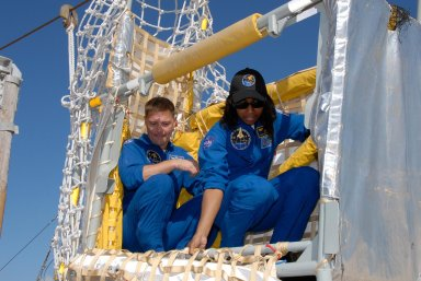 KENNEDY SPACE CENTER, FLA. -- During emergency egress training as part of the pre-launch terminal countdown demonstration test, or TCDT, STS-120 crew members learn how to get out of the slidewire basket at the landing site. In the basket are Mission Specialists Doug Wheelock and Stephanie Wilson. The TCDT provides astronauts and ground crews an opportunity to participate in various simulated countdown activities, including equipment familiarization and emergency training. The STS-120 mission will deliver the U.S. Node 2 module, named Harmony, aboard space shuttle Discovery to the International Space Station. Launch of Discovery on mission STS-120 is targeted for Oct. 23 at 11:38 a.m. EDT on a 14-day mission. Photo credit: NASA/Kim Shiflett