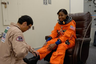 KENNEDY SPACE CENTER, FLA. -- STS-120 Mission Specialist Stephanie Wilson is helped with her boot during suitup for a simulated launch countdown, part of the prelaunch terminal countdown demonstration test, or TCDT. Her name patch reflects the nicknames the crew gave each other for the event. The TCDT provides astronauts and ground crews an opportunity to participate in various launch preparation activities, including equipment familiarization, emergency training and the simulated countdown. The STS-120 mission will deliver the U.S. Node 2 module, named Harmony, aboard space shuttle Discovery to the International Space Station. Launch of Discovery on mission STS-120 is targeted for Oct. 23 at 11:38 a.m. EDT on a 14-day mission. Photo credit: NASA/Kim Shiflett