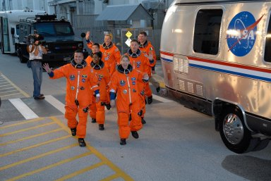 KENNEDY SPACE CENTER, FLA. -- At the Operations and Checkout Building, the crew members of space shuttle mission STS-120 prepare to board the bus that will transport them to Launch Pad 39A during their terminal countdown demonstration test activities. In the left row are, from front, Pilot George Zamka and Mission Specialists Stephanie Wilson, Daniel Tani, and Scott Parazynski. In the right row are, from front, Commander Pam Melroy and Mission Specialists Doug Wheelock and Paolo Nespoli. Nespoli represents the European Space Agency. After the mission, Tani will remain aboard the International Space Station and return with the STS-122 crew, targeted to launch Dec. 6. The terminal countdown demonstration test provides astronauts and ground crews an opportunity to participate in various simulated countdown activities, including equipment familiarization and emergency training. The STS-120 mission will deliver the U.S. Node 2 module, named Harmony, aboard space shuttle Discovery to the ISS. Discovery's launch is targeted for Oct. 23 at 11:38 a.m. EDT on a 14-day mission. Photo credit: NASA/Kim Shiflett