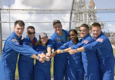 KENNEDY SPACE CENTER, FLA. -- At NASA's Kennedy Space Center, the STS-120 crew shows solidarity and enthusiasm during an excursion to the launch pad the day before launch. From left are Mission Specialist Paolo Nespoli, Pilot George Zamka, Commander Pamela Melroy and Mission Specialists Scott Parazynski, Stephanie Wilson, Daniel Tani and Doug Wheelock. Nespoli represents the European Space Agency. Tani will be remaining on the International Space Station to join the Expedition 16 crew after the mission is complete. Liftoff of space shuttle Discovery is scheduled for 11:38 a.m. EDT Oct. 23. The mission will be the 23rd assembly flight to the International Space Station and the 34th flight for Discovery. Payload on the mission is the Italian-built U.S. Node 2, called Harmony. On the 14-day mission, the crew will install Harmony and move the P6 solar arrays to their permanent position and deploy them. Discovery is expected to complete its mission and return home at 4:47 a.m. EST on Nov. 6. Photo credit: NASA/Kim Shiflett