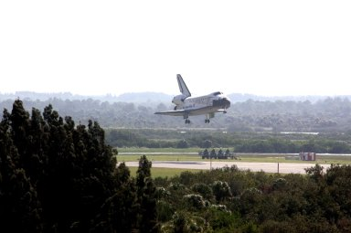 KENNEDY SPACE CENTER, FLA. -- Space shuttle Discovery sinks below the tree line as it approaches landing on Runway 33 of the Shuttle Landing Facility at NASA's Kennedy Space Center, concluding the 15-day mission STS-120. Commander Pamela Melroy is at the controls, along with Pilot George Zamka. Main gear touchdown was 1:01:16 p.m. Wheel stop was at 1:02:07 p.m. Mission elapsed time was 15 days, 2 hours, 24 minutes and 2 seconds. Mission STS-120 continued the construction of the station with the installation of the Harmony Node 2 module and the relocation of the P6 truss. Photo credit: NASA/Scott Haun