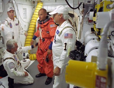 KENNEDY SPACE CENTER, FLA. -- STS-117 Commander Frederick Sturckow is helped by the closeout crew in the White Room on Launch Pad 39A to secure his launch suit before climbing into Space Shuttle Atlantis. The mission to the International Space Station is scheduled to launch at 7:38 p.m. EDT. Members of the Closeout Crew help the astronauts don a parachute pack, strap them into the space shuttle's crew module and take care of any other last-minute needs that arise. The White Room is at the end of the orbiter access arm that extends from the fixed service structure and provides entry into the orbiter. The shuttle is delivering a new segment to the starboard side of the space station's backbone, known as the truss. Three spacewalks are planned to install the S3/S4 truss segment, deploy a set of solar arrays and prepare them for operation. STS-117 is the 118th space shuttle flight, the 21st flight to the station, the 28th flight for Atlantis and the first of four flights planned for 2007. Photo credit: NASA/Tony Gray & Don Kight