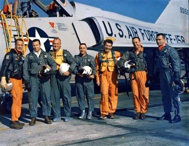 "KENNEDY SPACE CENTER, FLA. -- The Original Seven Mercury Astronauts pose beside an Air Force F-102 jet. Standing, left to right, are Scott Carpenter, L. Gordon Cooper, John H. Glenn, Virgil I. ""Gus"" Grissom, Walter H. Schirra Jr., Alan B. Shepherd Jr., and Donald K. Slayton."