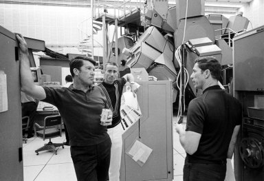 KENNEDY SPACE CENTER, FLA. -- Apollo 7 astronauts, left to right, Walter Schirra, Walter Cunningham and Donn Eisele pause during a practice mission yesterday within Kennedy Space Center's Flight Crew Training Building. The trio spent several hours in the Apollo mission simulator, rear, in preparation for their upcoming mission. The National Aeronautics and Space Administration's first manned Apollo flight is scheduled to begin no earlier than Oct. 11, 1968.