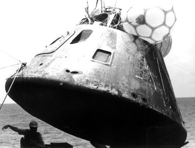 KENNEDY SPACE CENTER, FLA. -- The ASTP Apollo Command Module is lowered onto the deck of the USS New Orleans following splashdown in the Pacific Ocean, west of Hawaii, at 5:18 p.m. today. Once aboard the ship, the ASTP astronauts Thomas Stafford, Vance Brand, and Donald Slayton emerged from the spacecraft and participated in ceremonies during which they spoke by telephone to President Gerald Ford. The splashdown ended the crew's historic nine-day mission, highlighted by their rendezvous and docking with a Soviet Soyuz spacecraft while in Earth orbit.