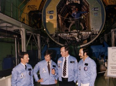 KENNEDY SPACE CENTER, FLA. -- Vice President George H.W. Bush, third from left, is pictured with the Spacelab engineering module at the Spacelab Arrival Ceremony in the Operations and Checkout Building as he visits with, from left, astronaut Claude Nicollier, European Space Agency, and payload specialists Ulf Marbod, West Germany, and Wubbo Ockels, the Netherlands. Overhead, in the module, is Owen K. Garriott, U.S. astronaut. The European-built Spacelab, designed to provide a shirt-sleeve environment for scientists working in Earth orbit, is scheduled to fly its first mission in the payload bay of the Space Shuttle in 1983.