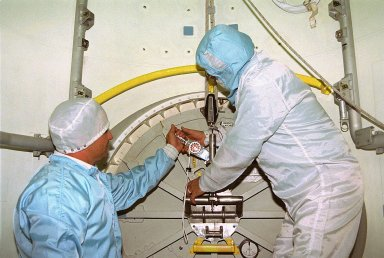 KENNEDY SPACE CENTER, FLA. -- In Orbiter Processing Facility Bay 1, United Space Alliance (USA) technicians Dave Lawrence, at left, and James Cullop troubleshoot the orbiter Columbia?s outer hatch of the airlock, which failed to open during the recent STS-80 Space Shuttle mission. Mission Specialists Tamara E. Jernigan and Thomas D. Jones did not perform the mission?s planned two extravehicular activities (EVAs) or spacewalks because the hatch would not open on orbit. The spacewalks were to be part of the continuing series of EVA Development Flight Tests to evaluate equipment and procedures and to build spacewalking experience in preparation for the International Space Station.