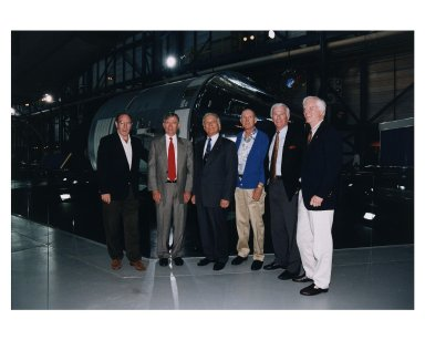 """KENNEDY SPACE CENTER, FLA. -- Some of the former Apollo program astronauts pose in front of an Apollo Command and Service Module during a tour the new Apollo/Saturn V Center (ASVC) at KSC prior to the gala grand opening ceremony for the facility that was held Jan. 8, 1997. The astronauts were invited to participate in the event, which also featured NASA Administrator Dan Goldin and KSC Director Jay Honeycutt. The astronauts are (from left): Apollo 14 Lunar Module Pilot Edgar D. Mitchell; Apollo 10 Command Module Pilot and Apollo 16 Commander John W. Young; Apollo 11 Lunar Module Pilot Edwin E. """"Buzz"""" Aldrin, Jr.; Apollo 10 Commander Thomas P. Stafford; Apollo 10 Lunar Module Pilot and Apollo 17 Commander Eugene A. Cernan; and Apollo 9 Lunar Module Pilot Russell L. Schweikart. The ASVC also features several other Apollo program spacecraft components, multimedia presentations and a simulated Apollo/Saturn V liftoff. The facility will be a part of the KSC bus tour that embarks from the KSC Visitor Center"""