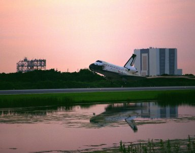 KENNEDY SPACE CENTER, FLA. -- Framed by the Vehicle Assembly Building at right and the Mate-Demate Device at left, the Space Shuttle orbiter Columbia glides onto Runway 33 at KSC?s Shuttle Landing Facility at 6:46:34 a.m. EDT with Mission Commander James D. Halsell Jr. and Pilot Susan L. Still at the controls to complete the STS-94 mission. Also on board are Mission Specialist Donald A. Thomas, Mission Specialist Michael L. Gernhardt, Payload Commander Janice Voss, and Payload Specialists Roger K. Crouch and Gregory T. Linteris. During the Microgravity Science Laboratory-1 (MSL-1) mission, the Spacelab module was used to test some of the hardware, facilities and procedures that are planned for use on the International Space Station while the flight crew conducted combustion, protein crystal growth and materials processing experiments. This mission was a reflight of the STS-83 mission that lifted off from KSC in April of this year. That space flight was cut short due to indications of a faulty fuel cell. This was Columbia?s 11th landing at KSC and the 38th landing at the space center in the history of the Shuttle program