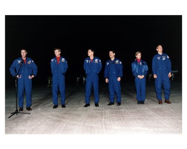 """The STS-81 flight crew conducts a press briefing on the runway of KSC's Shuttle Landing Facility after they arrive at the space center for the final countdown preparations for the fifth Shuttle-Mir docking mission. They are (from left): Mission Commander Michael A. Baker; Pilot Brent W. Jett, Jr.; and Mission Specialists Peter J. K. """"Jeff"""" Wisoff; John M. Grunsfeld, Marsha S. Ivins, and J.M. """"Jerry"""" Linenger. The 10-day mission will feature the transfer of Linenger to Mir to replace astronaut John Blaha, who has been on the orbital laboratory since Sept. 19, 1996 after arrival there during the STS79 mission. During STS-81, Shuttle and Mir crews will conduct risk mitigation, human life science, microgravity and materials processing experiments that will provide data for the design, development and operation of the International Space Station. The primary payload is the SPACEHAB-DM double module which will provide space for more than 2,000 pounds of hardware, food and water that will be transferred into the Russian space station during five days of docking operations. The SPACEHAB will also be used to return experiment samples from the Mir to Earth for analysis and for microgravity experiments during the mission"""