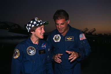 STS-86 Mission Specialists Wendy B. Lawrence, at left, and David A. Wolf confer possibly about the Russian Space Station Mir? after their arrival at KSC?s Shuttle Landing Facility for the Terminal Countdown Demonstration Test (TCDT). Lawrence was supposed to be the next U.S. astronaut slated for a long-duration stay aboard Mir, but was replaced by Wolf in late July. Unlike Lawrence, Wolf has undergone spacewalk training and fits in the Orlan spacesuit used by Russians on spacewalks. Lawrence will remain on the STS-86 crew, but will return to Earth at the conclusion of the planned 10-day mission. Wolf will take the place on Mir of astronaut C. Michael Foale, who arrived on the Russian space station during the STS-84 mission in May. STS-86 will be the seventh docking of the Space Shuttle with the Mir. The mission is targeted for a Sept. 25 launch aboard the Space Shuttle Atlantis