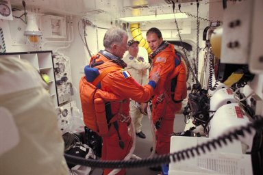 While a white room closeout crew member looks on, STS-86 Pilot Michael J. Bloomfield, at right, gets some assistance from fellow crew member, Mission Specialist Jean-Loup J.M. Chretien of the French Space Agency, CNES, before entering the Space Shuttle Atlantis at Launch Pad 39A