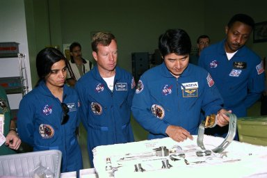 STS-87 astronaut crew members participate in the Crew Equipment Integration Test (CEIT) in Kennedy Space Center?s (KSC's) Vertical Processing Facility. From left are Mission Specialist Kalpana Chawla, Ph.D.; Pilot Steven Lindsey; Mission Specialist Takao Doi , Ph.D., of the National Space Development Agency of Japan; and Mission Specialist Winston Scott. The CEIT gives astronauts an opportunity to get a hands-on look at the payloads with which they will be working onorbit. STS-87 will be the fourth United States Microgravity Payload and flight of the Spartan-201 deployable satellite. During the STS-87 mission, scheduled for a Nov. 19 liftoff from KSC, Dr. Doi and Scott will both perform spacewalks