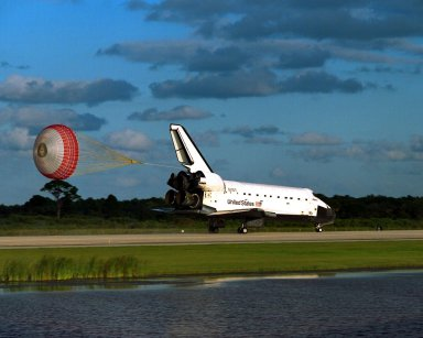 KENNEDY SPACE CENTER, Fla. -- The orbiter drag chute deploys after the Space Shuttle orbiter Atlantis lands on Runway 15 of the KSC Shuttle Landing Facility (SLF) at the conclusion of the nearly 11-day STS-86 mission. Main gear touchdown was at 5:55:09 p.m. EDT, Oct. 6, 1997, with an unofficial mission-elapsed time of 10 days, 19 hours, 20 minutes and 50 seconds. The first two KSC landing opportunities on Sunday were waved off because of weather concerns. The 87th Space Shuttle mission was the 40th landing of the Shuttle at KSC. On Sunday evening, the Space Shuttle program reached a milestone: The total flight time of the Shuttle passed the two-year mark. STS86 was the seventh of nine planned dockings of the Space Shuttle with the Russian Space Station Mir. STS-86 Mission Specialist David A. Wolf replaced NASA astronaut and Mir 24 crew member C. Michael Foale, who has been on the Mir since mid-May. Foale returned to Earth on Atlantis with the remainder of the STS-86 crew. The other crew members are Commander James D. Wetherbee, Pilot Michael J. Bloomfield, and Mission Specialists Wendy B. Lawrence, Scott E. Parazynski, Vladimir Georgievich Titov of the Russian Space Agency, and Jean-Loup J.M. Chretien of the French Space Agency, CNES. Wolf is scheduled to remain on the Mir until the STS-89 Shuttle mission in January. Besides the docking and crew exchange, STS-86 included the transfer of more than three-and-a-half tons of science/logistical equipment and supplies between the two orbiting spacecraft. Parazynski and Titov also conducted a spacewalk while Atlantis and the Mir were docked
