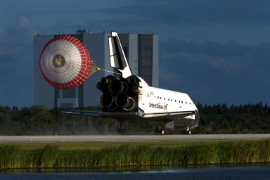 KENNEDY SPACE CENTER, Fla. -- The orbiter drag chute deploys after the Space Shuttle orbiter Atlantis lands on Runway 15 of the KSC Shuttle Landing Facility (SLF) at the conclusion of the nearly 11-day STS-86 mission. The Vehicle Assembly Building (VAB) can be seen in the background. Main gear touchdown was at 5:55:09 p.m. EDT, Oct. 6, 1997, with an unofficial mission-elapsed time of 10 days, 19 hours, 20 minutes and 50 seconds. The first two KSC landing opportunities on Sunday were waved off because of weather concerns. The 87th Space Shuttle mission was the 40th landing of the Shuttle at KSC. On Sunday evening, the Space Shuttle program reached a milestone: The total flight time of the Shuttle passed the two-year mark. STS86 was the seventh of nine planned dockings of the Space Shuttle with the Russian Space Station Mir. STS-86 Mission Specialist David A. Wolf replaced NASA astronaut and Mir 24 crew member C. Michael Foale, who has been on the Mir since mid-May. Foale returned to Earth on Atlantis with the remainder of the STS-86 crew. The other crew members are Commander James D. Wetherbee, Pilot Michael J. Bloomfield, and Mission Specialists Wendy B. Lawrence, Scott E. Parazynski, Vladimir Georgievich Titov of the Russian Space Agency, and Jean-Loup J.M. Chretien of the French Space Agency, CNES. Wolf is scheduled to remain on the Mir until the STS-89 Shuttle mission in January. Besides the docking and crew exchange, STS-86 included the transfer of more than three-and-a-half tons of science/logistical equipment and supplies between the two orbiting spacecraft. Parazynski and Titov also conducted a spacewalk while Atlantis and the Mir were docked