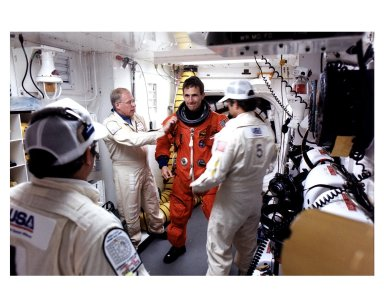 Mission Specialist Jerry Linenger prepares to enter the Space Shuttle Atlantis at Launch Pad 39B with help from white room close out members Jim Mangione(left foreground),Danny Wyatt and Jim Martin