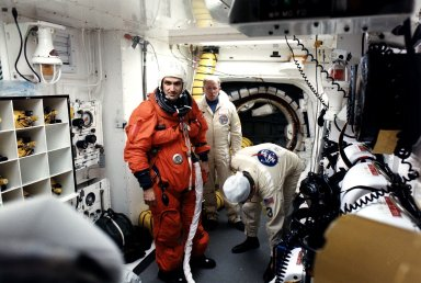 KENNEDY SPACE CENTER, FLA. - STS-81 Mission Specialist Jeff Wisoff prepares to enter the Space Shuttle Atlantis at Launch Pad 39B with help from White Room closeout crew members Danny Wyatt (center) and Al Rochford.