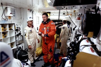 KENNEDY SPACE CENTER, FLA. - STS-81 Mission Commander Michael Baker prepares to enter the Space Shuttle Atlantis at Launch Pad 39B with help from White Room closeout crew members Chris Meinert (left) and Danny Wyatt.