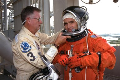 STS-87 Payload Specialist Leonid Kadenyuk, at right, of the National Space Agency of Ukraine (NSAU) is assisted into his orange launch and entry spacesuit ensemble by NASA Suit Technician Al Rochford, at left, before participating in Terminal Countdown Demonstration Test (TCDT) activities. The crew of the STS-87 mission is scheduled for launch Nov. 19 aboard the Space Shuttle Columbia. The TCDT is held at KSC prior to each Space Shuttle flight providing the crew of each mission opportunities to participate in simulated countdown activities. The TCDT ends with a mock launch countdown culminating in a simulated main engine cut-off. The crew also spends time undergoing emergency egress training exercises at the pad and has an opportunity to view and inspect the payloads in the orbiter's payload bay