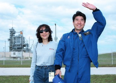 STS-87 Mission Specialist Takao Doi, Ph.D., of the National Space Development Agency of Japan poses with his wife, Hitomi Doi, in front of Kennedy Space Center's Launch Pad 39B during final prelaunch activities leading up to the scheduled Nov. 19 liftoff. The other STS-87 crew members are Commander Kevin Kregel; Pilot Steven Lindsey; Mission Specialists Kalpana Chawla, Ph.D., and Winston Scott; and Payload Specialist Leonid Kadenyuk of the National Space Agency of Ukraine. STS-87 will be the fourth flight of the United States Microgravity Payload and the Spartan-201 deployable satellite