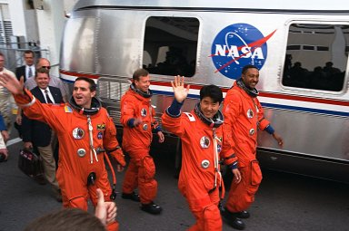 The crew of Mission STS-87 depart from the Operations and Checkout Building en route to Launch Pad 39B, where the Space Shuttle Columbia awaits liftoff on the fourth flight of the United States Microgravity Payload and the Spartan-201 deployable satellite. They are, from left to right, front to back: Mission Specialist Takao Doi, Ph.D., of the National Space Development Agency of Japan; Mission Specialist Winston Scott (near van); Payload Specialist Leonid Kadenyuk of the National Space Agency of Ukraine; and Pilot Steven Lindsey (near van). Missing from this photo are Commander Kevin Kregel and Mission Specialist Kalpana Chawla, Ph.D. The Space Shuttle Columbia and its crew of six members are scheduled to lift off during a two-and-a-half hour launch window, which opens at 2:46 p.m