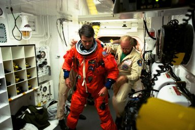STS-87 Commander Kevin Kregel is assisted with his ascent and re-entry flight suit in the white room at Launch Pad 39B by Danny Wyatt, NASA quality assurance specialist. STS-87 is the fourth flight of the United States Microgravity Payload and Spartan-201. A veteran of two space flights (STS-70 and -78), Kregel has logged more than 618 hours in space