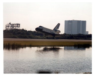 """KENNEDY SPACE CENTER, FLA. -- With the Mate/Demate Device (MDD) on the left and the Vehicle Assembly Building (VAB) on the right, the Space Shuttle orbiter Atlantis approaches Runway 33 at KSC?s Shuttle Landing Facility for a scheduled touchdown at about 9:23 a.m. EST Jan. 22. When the orbiter lands, it will conclude the fifth Shuttle-Mir docking mission and return NASA astronaut John Blaha to Earth after four months in space. At main gear touchdown, the STS-81 mission duration will be 10 days, 4 hours, 55 minutes. This is the 34th KSC landing in Shuttle history. Mission Commander Michael A. Baker is steering Atlantis to a perfect landing, with help from Pilot Brent W. Jett, Jr. Other returning STS-81 crew members are Mission Specialists John M. Grunsfeld, Peter J. K. """"Jeff"""" Wisoff and Marsha S. Ivins. Atlantis also brought back experiment samples from the Russian space station Mir for analysis on Earth"""